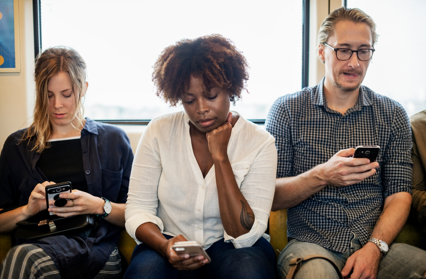 Image of three people busy with their phone